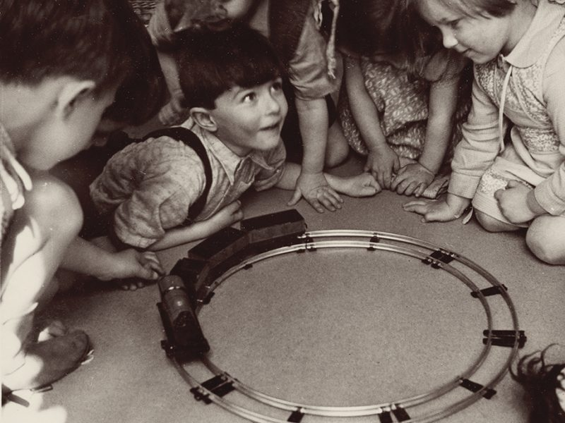Black and white photograph of a group of children playing with a trainset