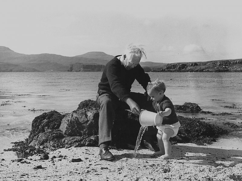 Black and white photograph of a small child playing on a beach with an elderly gentleman