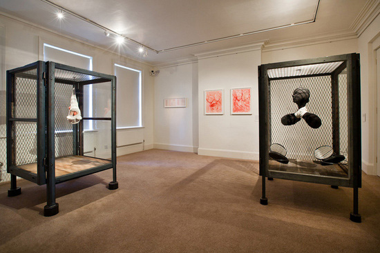 Exhibits by Louise Bourgeois stand in two display cases in a gallery