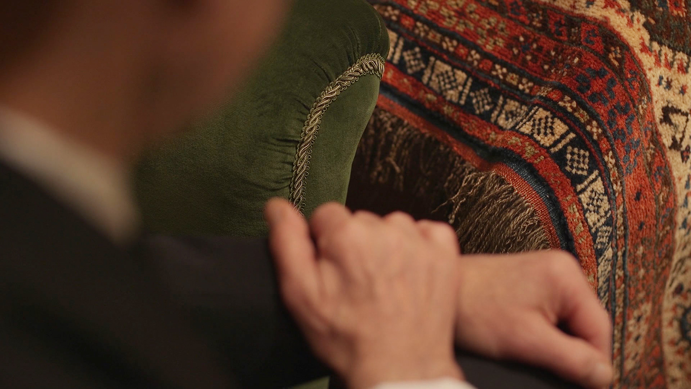 Photographing detailing a man's hands next to Freud's couch