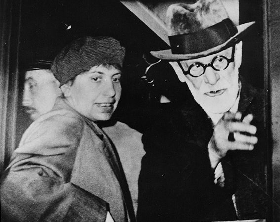 Black and white photograph of Anna and Sigmund Freud looking out of a train window.