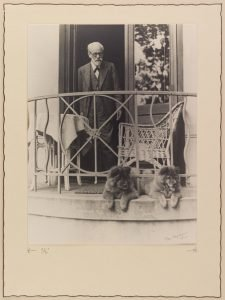 Black and white photograph of Sigmund Freud in the doorway of a balcony with dogs in foreground.