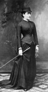 Black and white photograph of a woman wearing black clothing and holding a cane.
