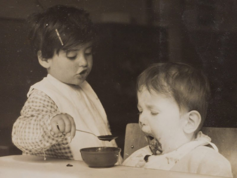 Sepia photograph of a child feeding another at the Jackson Nursery