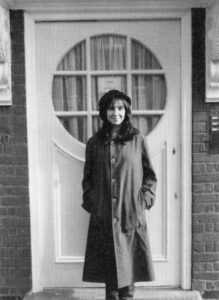 Black and white photograph of Sophie Calle standing in front of the front door of the Freud Museum London.